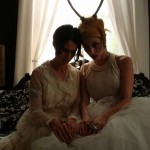 Carolyn Ryder Cooley and Sarah Zar.  Two ladies sitting together in a Victorian Interior portrait in Athens, NY. The women wear white lace wedding dresses and antlers.